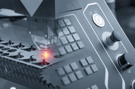 Abstracte scène van de laser snijder machine met het bedieningspaneel tijdens het snijden van het plaatwerk met het vonkend licht effect.