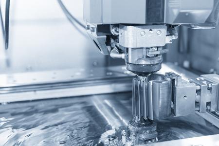 Abstracte scène van de close-up van de draad - EDM CNC-machine terwijl u de werkstukken van de steekproef in lichtblauwe toon en bedieningspaneel snijdt Stockfoto