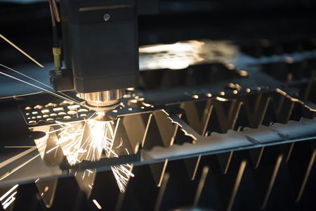 La máquina cortadora de láser mientras corta la chapa con la luz de chispas Foto de archivo - 73520085