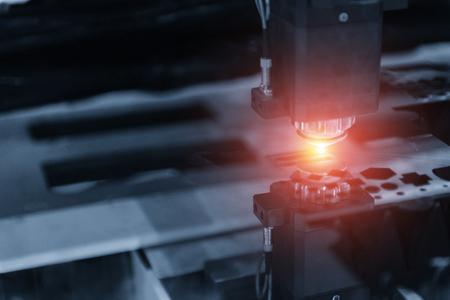 De CNC lasersnijmachine terwijl het plaatmetaal met het vonklicht wordt gesneden. Het snijproces met hoge nauwkeurigheid door laser snijden Stockfoto
