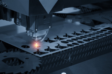 The CNC laser cut machine while cutting the sheet metal with the sparking light.The hi-precision sheet cutting process by laser cut Stockfoto
