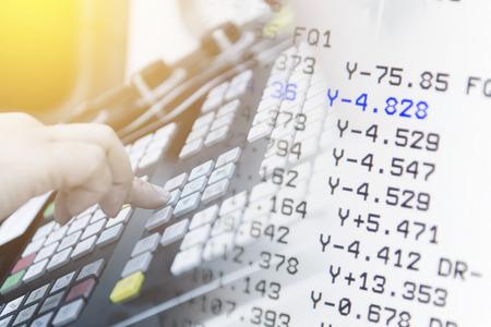 De hand drukt op de knop op het CNC bedieningspaneel met de NC data Stockfoto - 75047444