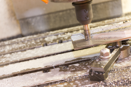 milling center: The CNC milling machine cutting the part with the coolant Stock Photo