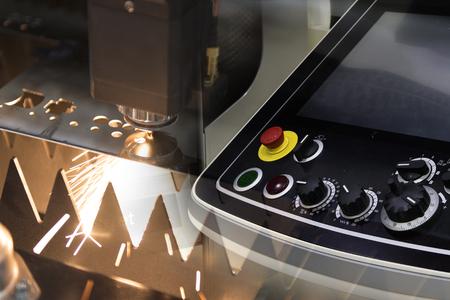 The CNC laser cut machine while cutting the sheet metal with the sparking light and the control panel .The hi-precision sheet cutting process by laser cut Stock Photo - 76526972