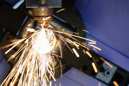 cutting: The CNC laser cut machine while cutting the steel tube  with the sparking light.The hi-precision tube cutting process by laser cut Stock Photo