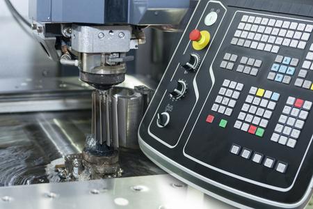 와이어의 근접 촬영의 추상 장면 - EDM CNC 기계 라이트 블루 톤과 컨트롤러 패널의 샘플 작업 조각을 절단하면서 스톡 콘텐츠
