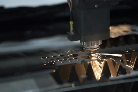 De laser snijmachine terwijl het plaatmetaal met het vonklicht wordt gesneden Stockfoto
