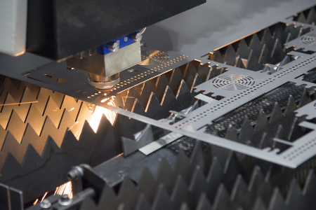 cutter: The laser cutter machine while cutting the sheet metal with the sparking light