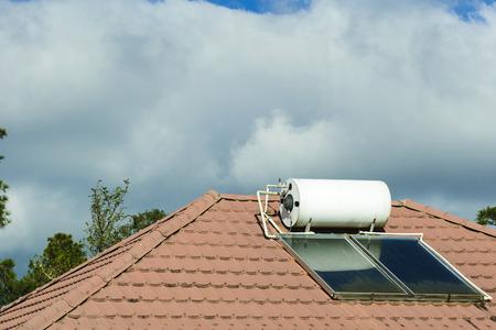 De zonneboiler op het dak van het huis met de wolk. Het concept van het milieubehoud.