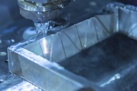 the workpiece: Close-up of the wire - EDM CNC machine while cutting the sample work pieces in light blue tone and lighting effect