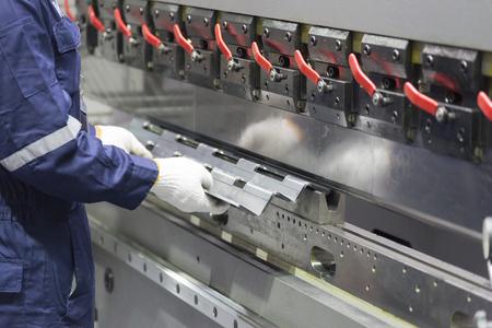 De technicusbedrijf gebruikt hydraulische buigmachine. Metalen werkconcept
