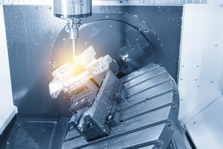 The five-axis Computer Numerical Control (CNC) machine while cutting sample aerospace part,turbine in the light blue scene. Stockfoto
