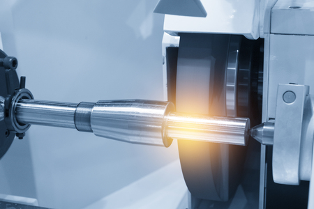 The cylindrical grinding machine with the steel shaft.Hi precision manufacturing concept. Stock Photo