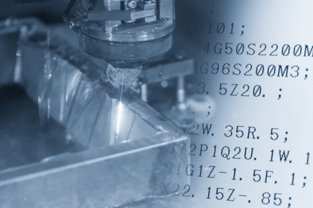 the workpiece: Close-up of the wire - EDM CNC machine  cutting the sample work pieces and the NC program data in light blue tone.Hi-technology manufacturing concept. Stock Photo