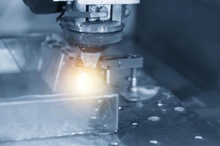 라이트 블루 톤 및 조명 효과 샘플 작업 조각을 절단하는 동안 와이어 -EDM CNC 기계의 근접