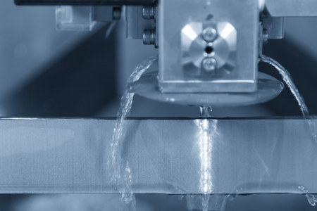Close-up of the wire - EDM CNC machine while cutting the sample work pieces in light blue tone  Archivio Fotografico