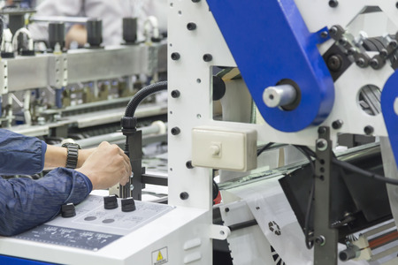 De technicus past de drukker aan. Het plastic zak productieproces.