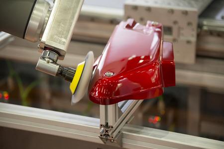 De robotarm polijst het automotive-onderdeel in de productielijn. Nieuwe technologie 4.0