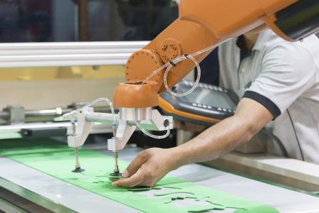 De technicusbediener past de automatische robotarm aan. Industrieel 4.0-concept. Moderne technologie voor productie