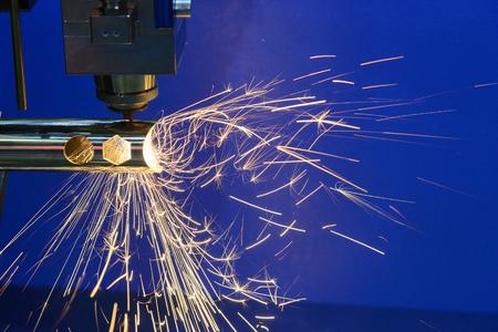 火花の光で鋼管を切断 CNC 繊維レーザー切断マシン。繊維レーザー加工機から炎。