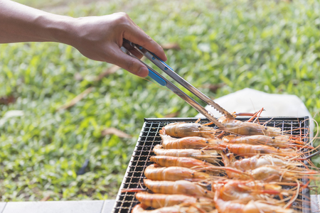 the hand of chef choose the grill shrimp