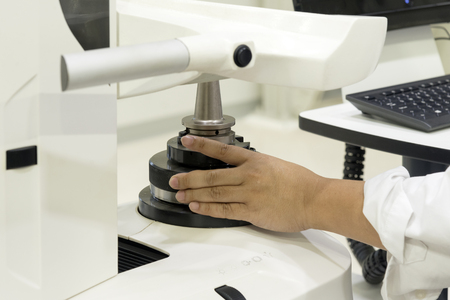 The hand of CNC operator setting the CNC holder for tool pre-setter  process. Calibration for CNC cutting tool. Stock Photo