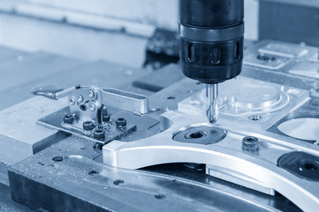 The CNC milling machine cutting cutting the raw material with the small ball-end mill tool .Hi-precision CNC machining concept. Stock Photo