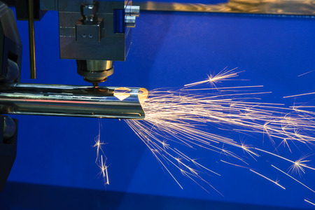 The fiber laser cutting machine cutting the steel pipe or tube with the sparking light.The fire flame from the fiber laser cutting machine. Stock Photo