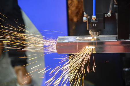 The laser cutting machine cutting the stainless tube.Tha sparking light from laser cutting machine. Stockfoto