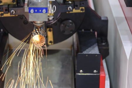 The laser cutting machine cutting the stainless tube.The sparking light from laser cutting machine.
