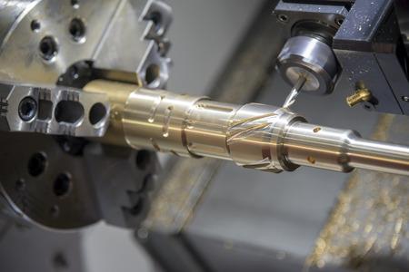 황동 샤프트를 절단하는 CNC 선반 (터닝 기계)의 닫습니다. 고정밀 CNC 머시닝 개념입니다.