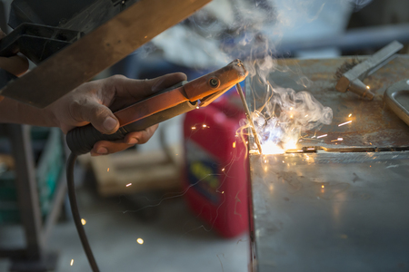 The worker welding the metal plate by electric welding  process.The sparking light from the arc welding process