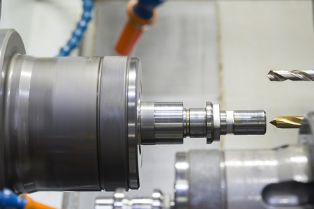 The  CNC lathe machine with the steel shaft .The  modern machining process.