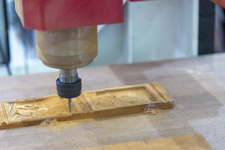 The CNC milling cutting the wood material.