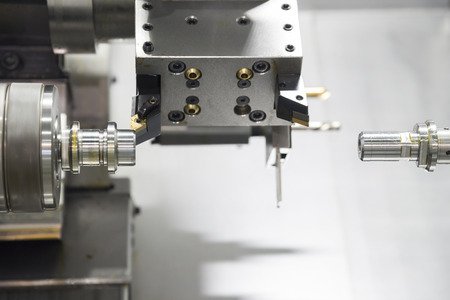 The  CNC lathe machine cutting the  metal shaft with the drill tool. 스톡 콘텐츠
