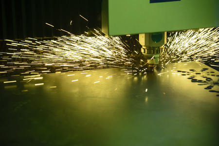 The fiber laser cutting the sheet metal plate with the sparking light.