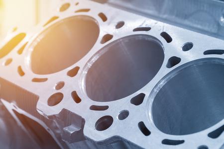 Close-up van het cilinderblok in de lichtblauwe scène. Autoonderdeel, machinedeel. Stockfoto
