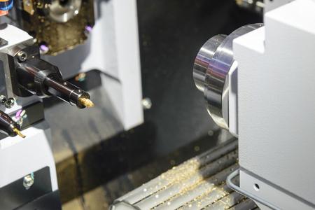 The CNC lathe machine cutting the brass rod shaft.