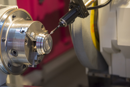 The CNC lathe machine cutting the metal part with the measurement probe.