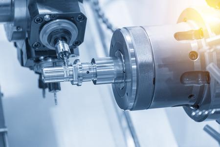 Die CNC-Drehmaschine fräst die Stahlwelle mittels Frässpindel. Standard-Bild