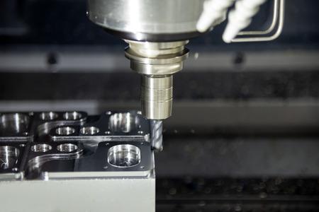 De CNC-freesmachine snijdt het metalen spuitgietdeel met het massieve vierkante vingerfreesgereedschap. Fabricageproces met hoge precisie. Stockfoto