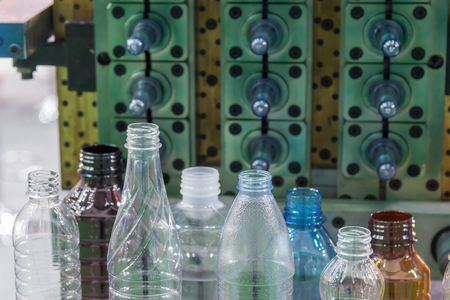 The various type of plastic bottle product with injection mold background.Drinking container manufacturing processing. Stock Photo