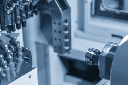 The small CNC turning or lathe machine cutting the metal shaft part in the light blue scene.