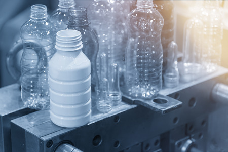 The various type of plastic bottle product with injection mold background in the light blue scene.Drinking container manufacturing processing. 写真素材