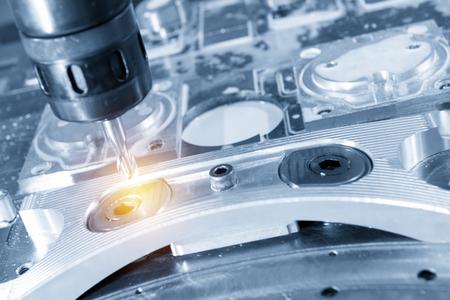 La fresadora CNC corta la pieza automotriz de aluminio con la fresa de bola sólida en la escena azul claro. Proceso de fabricación moderno. Foto de archivo