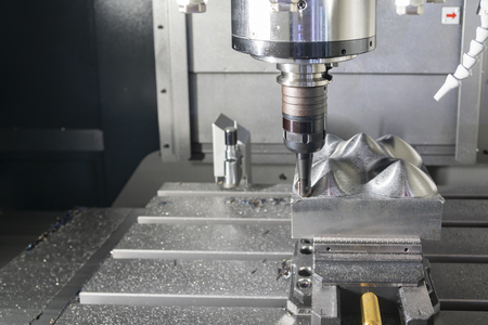 The CNC milling machine cutting the metal mold part with the index-able  ball endmill  tool. High technology mold manufacturing process.