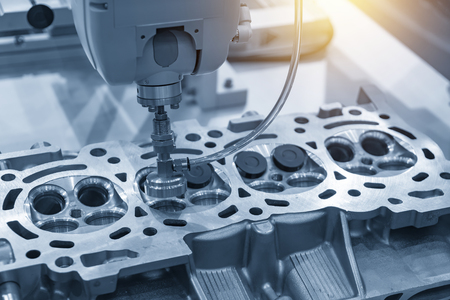 The boring machine make the hole at the cylinder head in the light blue scene.Automotive part manufacturing process .