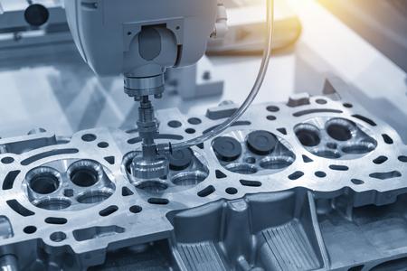Die Bohrmaschine bohrt das Loch am Zylinderkopf in die hellblaue Szene. Herstellungsprozess für Autoteile.