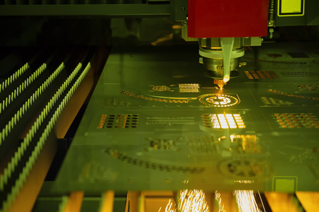The CNC fiber laser cutting machine cutting the metal plate with the sparking light. Modern sheet metal manufacturing process.
