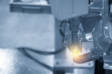 The welding robot machine for spot welding automotive part in the light blue scene.Industrial 4.0 concept for modern manufacturing process.